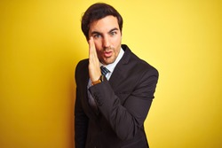Young handsome businessman wearing suit and tie standing over isolated yellow background hand on mouth telling secret rumor, whispering malicious talk conversation