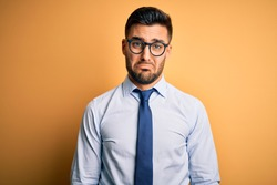 Young handsome businessman wearing tie and glasses standing over yellow background depressed and worry for distress, crying angry and afraid. Sad expression.