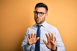 Young handsome businessman wearing tie and glasses standing over yellow background Moving away hands palms showing refusal and denial with afraid and disgusting expression. Stop and forbidden.