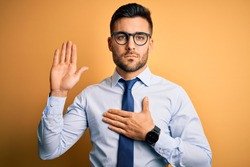 Young handsome businessman wearing tie and glasses standing over yellow background Swearing with hand on chest and open palm, making a loyalty promise oath