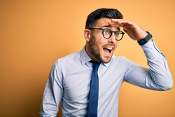 Young handsome businessman wearing tie and glasses standing over yellow background very happy and smiling looking far away with hand over head. Searching concept.