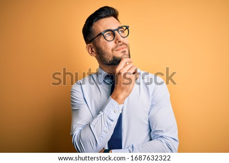 Young handsome businessman wearing tie and glasses standing over yellow background with hand on chin thinking about question, pensive expression. Smiling and thoughtful face. Doubt concept.