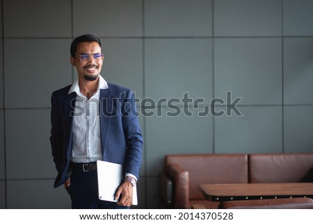 Young handsome businessman wears glasses and works on touchpad while sitting on sofa in office. Stock fotó ©