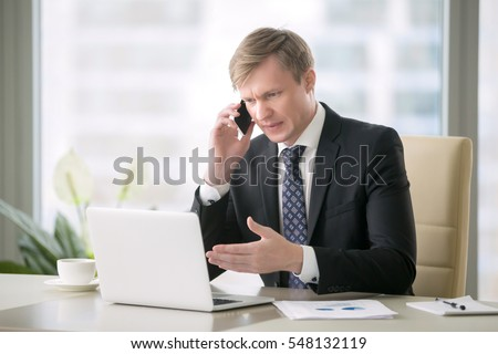 Young handsome businessman working with laptop at desk in the modern office, talking on phone, unexpected obstacles, risky business, getting a second opinion from another entrepreneur in whom confide