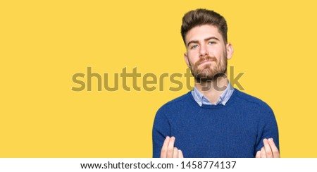 Young handsome bussines man Doing money gesture with hand, asking for salary payment, millionaire business