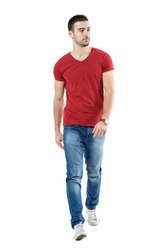 Young handsome casual man walk towards camera looking away. Full body length portrait isolated over white studio background.