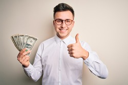 Young handsome caucasian business man holding bunch of one dollar banknotes happy with big smile doing ok sign, thumb up with fingers, excellent sign