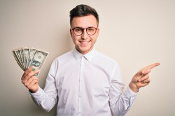 Young handsome caucasian business man holding bunch of one dollar banknotes very happy pointing with hand and finger to the side