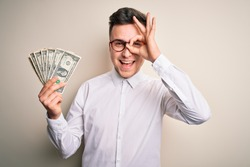 Young handsome caucasian business man holding bunch of one dollar banknotes with happy face smiling doing ok sign with hand on eye looking through fingers