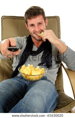 Young handsome caucasian man sitting on sofa holding a remote control and eating potatoes chips. Relaxation time. Studio shot. White background.