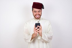 young handsome Caucasian man wearing Arab djellaba and Fez hat over white wall using mobile phone chatting free time .