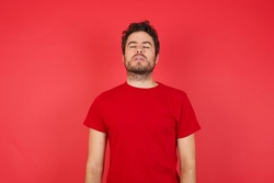 Young handsome caucasian man wearing t-shirt over isolated red background looking sleepy and tired, exhausted for fatigue and hangover, lazy eyes in the morning.