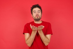 Young handsome caucasian man wearing t-shirt over isolated red background sending blow kiss with pout lips and holding palms to send air kiss.