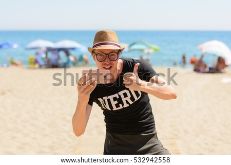 Young handsome Caucasian nerd taking picture and giving thumb up on vacation at beach in Spain