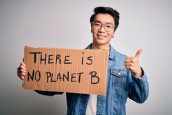 Young handsome chinese activist man protesting asking for care the planet on manifestation happy with big smile doing ok sign, thumb up with fingers, excellent sign