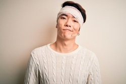 Young handsome chinese man injured for accident wearing bandage and strips on head looking sleepy and tired, exhausted for fatigue and hangover, lazy eyes in the morning.