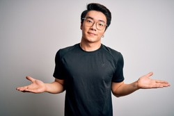 Young handsome chinese man wearing black t-shirt and glasses over white background clueless and confused expression with arms and hands raised. Doubt concept.