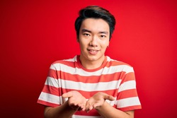 Young handsome chinese man wearing casual striped t-shirt standing over red background Smiling with hands palms together receiving or giving gesture. Hold and protection