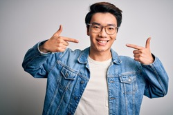 Young handsome chinese man wearing denim jacket and glasses over white background smiling cheerful showing and pointing with fingers teeth and mouth. Dental health concept.