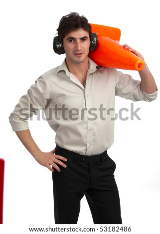 Young, handsome construction foreman with rolled-up sleeves, wearing hearing protection and carrying a traffic cone - stock photo