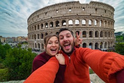 Young handsome couple at the Colosseum, Rome - Happy tourists visiting italian famous landmarks taking selfie photo