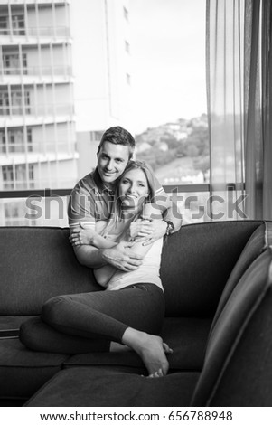 young handsome couple enjoys hugging on the sofa in their luxury home villa #656788948