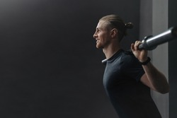 Young handsome crossfit athlete doing exercise with barbell in gym. Happy smiling man warming up and preparing before training. Crossfit, sport, bodybuilding and healthy lifestyle concept. Copy space