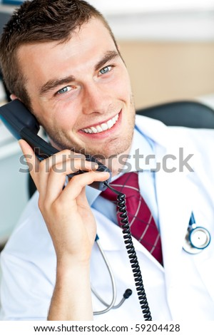 young handsome doctor on phone in his office smiling at the camera