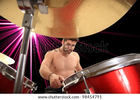 young handsome drummer portrait on laser effect background - stock photo