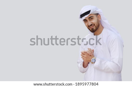 Young handsome Emirati business man in UAE traditional outfit showing a variety of hand gesture. Arabic ambitious mature businessman