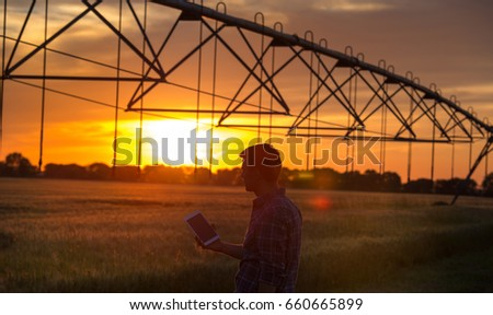 Young handsome farmer with tablet standing in wheat field at sunset with irrigation system in background