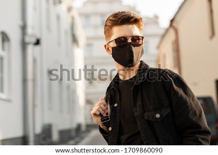 Young handsome fashion man in sunglasses with backpack in face pollution mask to protect himself from the coronavirus walking in city at sunset. Stylish guy in denim black clothes. Youth style 2020.