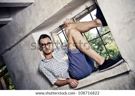 young handsome fashion model man lie in window - colorized photo