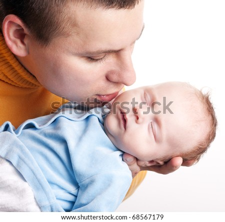 Young handsome father kissing his newborn baby isolated over white background. Little baby sleeping on fathers hands so sweetly in studio.