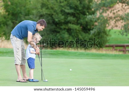 young handsome father teaching his little son how to play golf