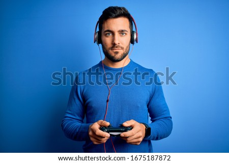 Young handsome gamer man with beard playing video game using joystick and headphones with a confident expression on smart face thinking serious