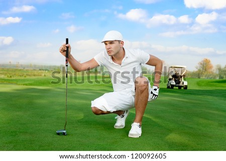 young handsome golfer on  a golf course