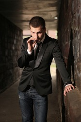 young handsome guy smoking in tunnel