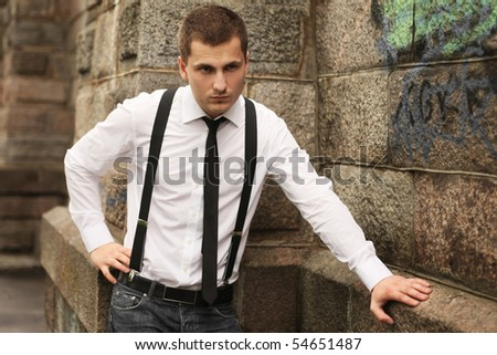 young handsome guy standing near brick wall - stock photo