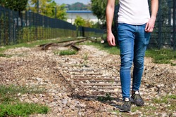Young handsome guy walking along old railway, enjoying his surroundings on sunny day. Traveler man on railroad. Following the old railway trail. Contemplating a trip by train. City style. Adventure.