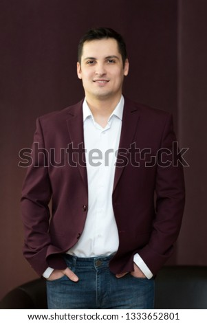 Young handsome guy with black hair. Male 25-30 years old in a white shirt in a dark jacket and jeans.