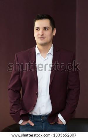 Young handsome guy with black hair. Male 25-30 years old in a white shirt in a dark jacket and jeans