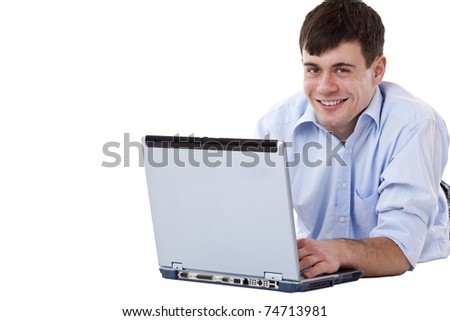 Young, handsome, happy man lying on floor with computer. Isolated on white background.