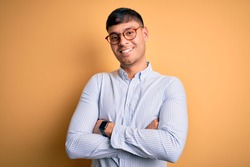 Young handsome hispanic business man wearing nerd glasses over yellow background happy face smiling with crossed arms looking at the camera. Positive person.