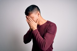 Young handsome hispanic man wearing casual shirt standing over white isolated background with sad expression covering face with hands while crying. Depression concept.