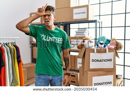 Young handsome hispanic man wearing volunteer t shirt at donations stand making fun of people with fingers on forehead doing loser gesture mocking and insulting.  Foto stock ©