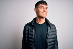 Young handsome hispanic man wearing winter coat standing over white isolated background looking away to side with smile on face, natural expression. Laughing confident.
