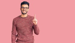 Young handsome hispanic man wearing winter sweater and glasses showing and pointing up with finger number one while smiling confident and happy.