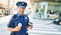 Young handsome hispanic policeman wearing police uniform smiling happy. Eating donut and drinking cup of take away coffee at town street.