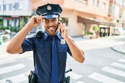 Young handsome hispanic policeman wearing police uniform smiling happy. Standing with smile on face having conversation talking on the smartphone at town street.